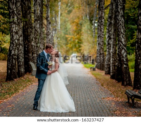 wedding couple hugging and kissing in a private moment of joy on a sunny autumn day - stock photo