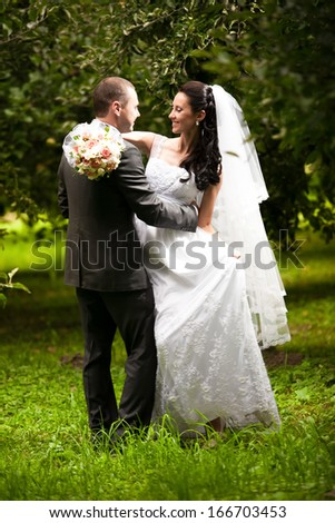 Wedding couple hugging and looking at each other at garden under trees - stock photo