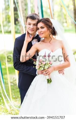 wedding couple hugging,  bride holding a bouquet of flowers, the groom embracing her - stock photo