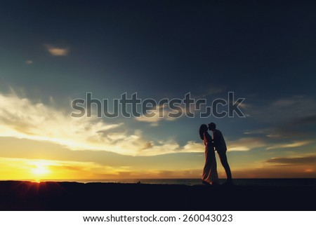 Wedding couple in Cuba in silhouettes, on background of sunset and sky - stock photo