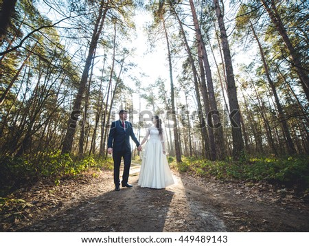 Wedding couple in forest.  happy wedding couple kissing and embracing in forest - stock photo