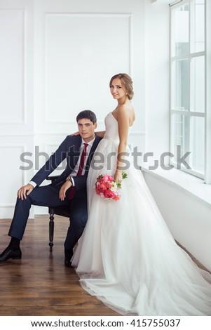 Wedding couple in love. Beautiful bride in white dress with brides bouquet and handsome groom in blue suite embrace indoors in decorated studio room, white bright interior with big window.  - stock photo