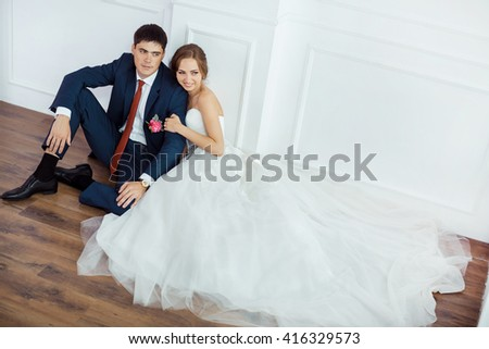 Wedding couple in love. Beautiful bride in white dress with brides bouquet and handsome groom in blue suite sitting on the floor and embracing each other indoors in decorated studio room, white bright - stock photo