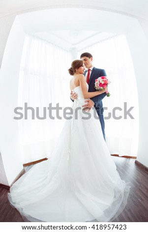 Wedding couple in love. Beautiful bride in white dress with brides bouquet and handsome groom in blue suit standing and embracing each other indoors at home, white bright room with big window High key - stock photo
