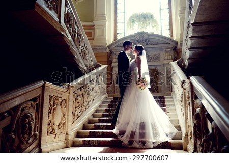 Wedding couple indoors is hugging each other. Beautiful model girl in white dress. Man in suit. Beauty bride with groom. Female and male portrait. Woman with lace veil. Cute lady and handsome guy - stock photo