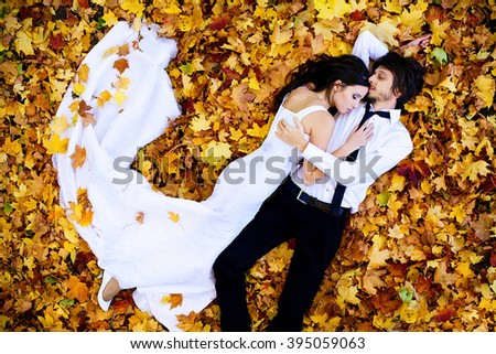 wedding couple , lying in a forest in autumn with orange leaves, white fish dress with a train - stock photo