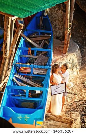 wedding couple near blue boat on exotic island - stock photo