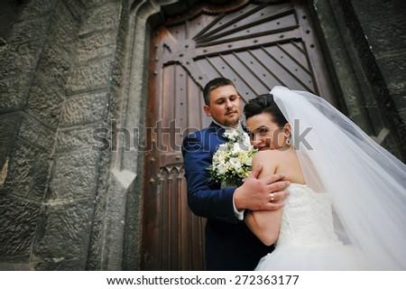 wedding couple near old catholic church - stock photo