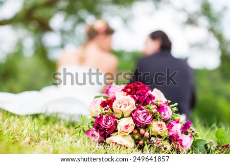 Wedding couple of bride and groom sitting on the meadow with bridal bouquet behind them, candid shot - stock photo