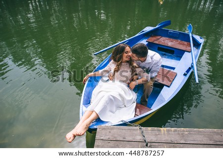 Wedding couple on a boat in the park - stock photo