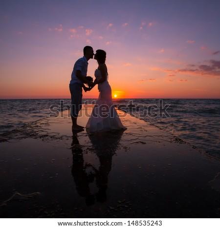 Wedding couple on the beach at sunset - stock photo