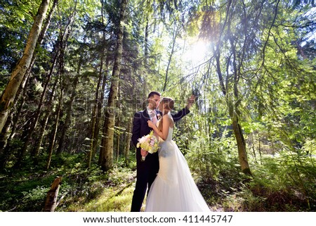 Wedding couple on the nature is hugging each other. Beautiful model girl in white dress. Man in suit. Beauty bride with groom. Female and male portrait. Woman with lace veil. Lady and guy outdoors - stock photo