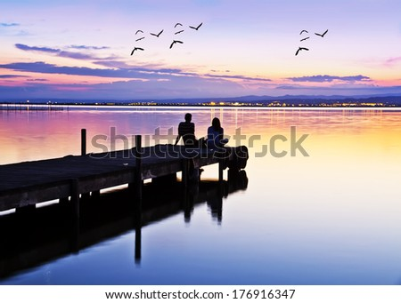 wedding couple on the pier watching the sunrise - stock photo