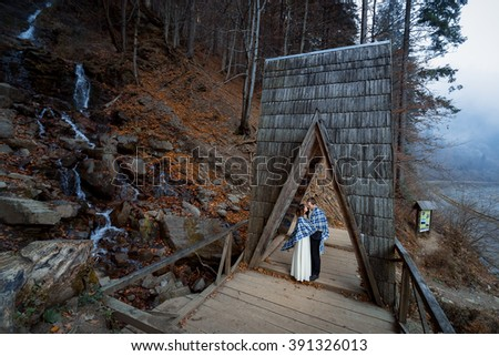 Wedding couple softly kiss on the wooden bridge. Misty day in mountains  - stock photo