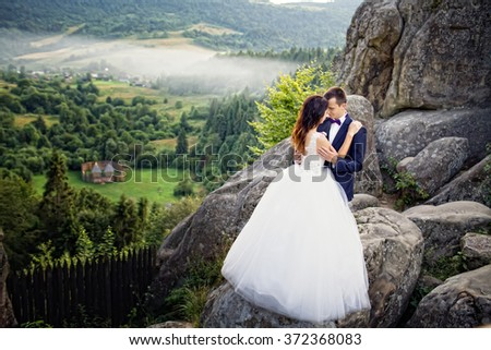 Wedding couple standing in the mountains against the sky. Cute romantic moment. Best day in the life of the bride. - stock photo