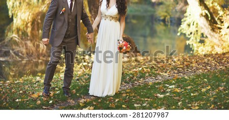 Wedding couple walking together in autumn forest. Fim effect color type. - stock photo