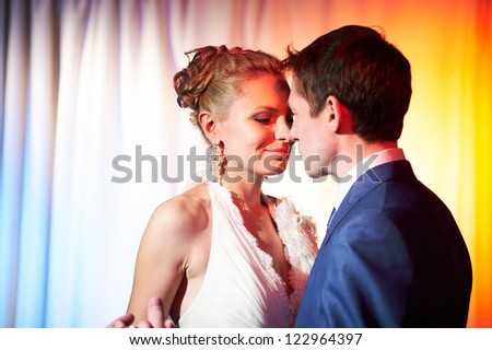 Wedding dance bride and groom in red light - stock photo