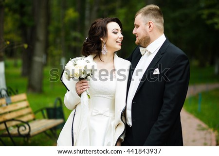 Wedding day: beautiful bride and groom in the park - stock photo