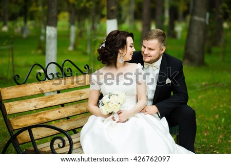 Wedding day: beautiful bride and groom sit on the bench in the park  - stock photo