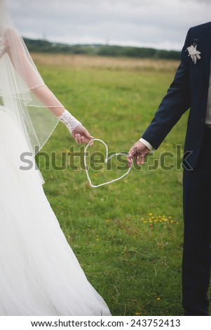 Wedding day. Bride and groom outdoor portrait with white heart. - stock photo