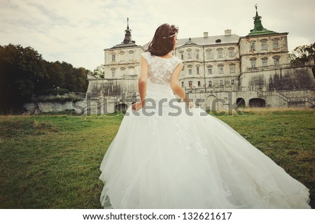 Wedding day. Gorgeous  bride walking next to castle in west Ukraine. - stock photo