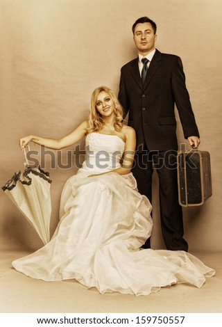 Wedding day. Portrait of married retro couple blonde bride with umbrella and groom with suitcase. Full length studio shot sepia color, vintage photo - stock photo