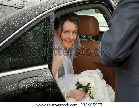 Wedding day: young charming bride looking out of a car - stock photo