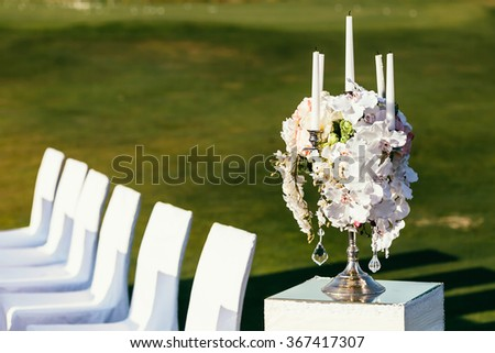 wedding decoration with flowers and candle on sunny day in ceremony place with white chairs - stock photo