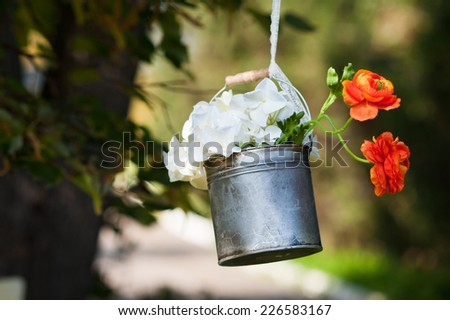 Wedding decoration with metal bucket and flowers - stock photo