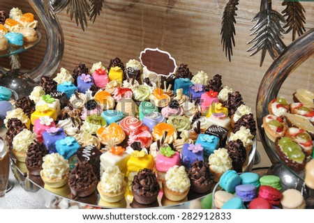 Wedding decoration with pastel colored cupcakes, meringues, muffins and macarons. Elegant and luxurious event arrangement with colorful macaroons. Wedding dessert with macaroons - stock photo