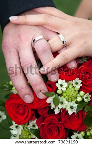 Wedding details - closeup of hands of newly-married with gold rings on wedding bouquet - stock photo
