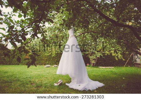 Wedding dress and shoes hanging on a tree in the park - stock photo