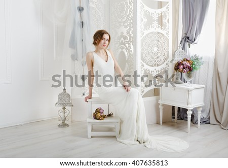 Wedding dress fashion. Beautiful young bride in vintage wedding dress indoors. White wedding dress at model. Girl shows wedding fashion in decorated interior with flowers, high key.  - stock photo