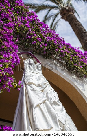 wedding dress on the wall with flowers - stock photo