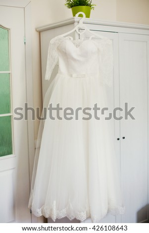 wedding dress on wooden hanger - stock photo