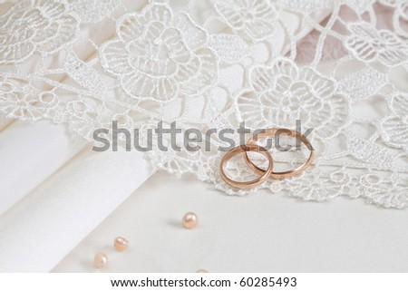 Wedding fabrics and lace and two gold rings. - stock photo