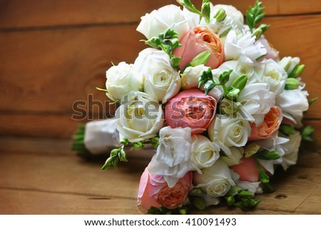 Wedding flower bouquet of roses and freesias on wooden background, selective focus - stock photo