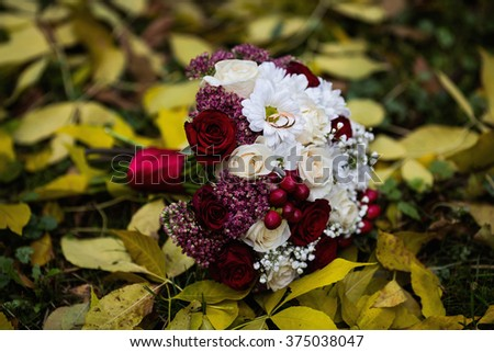 wedding flowers, wedding rings lie on a wedding bouquet, bouquet of red and peach, dairy roses and white flowers lying on yellow autumn leaves, wedding ceremony, come autumn, time of year, the grass - stock photo
