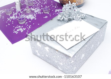 Wedding gifts on a plain white table with purple accent - stock photo