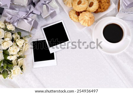 Wedding gifts with blank instant photo prints laid on bridal lace with several silver wedding gifts and white rose bouquet.  Space for copy. - stock photo
