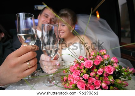 Wedding glasses with just married couple in limousine as a background - stock photo