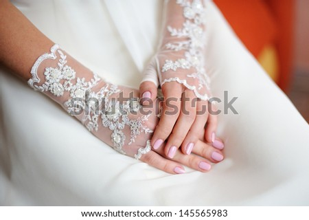 Wedding gloves on the hands of the bride - stock photo