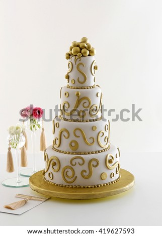 wedding gold cake with invitation card - stock photo