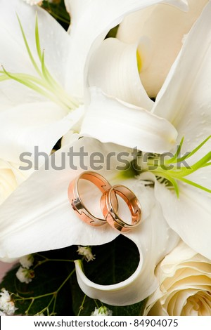 Wedding gold rings lie on a bunch of flowers for the bride - stock photo