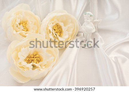 Wedding greeting card. Bridal satin cloth background with large flowers and an angel figurine. - stock photo