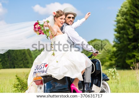 Wedding groom and bride driving motor scooter having fun, a just married sign attached  - stock photo