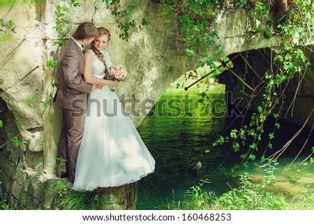 wedding, groom and bride hugging on a green lake - stock photo