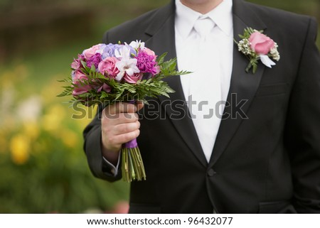 Wedding groom with bride's bouquet of flowers outside - stock photo