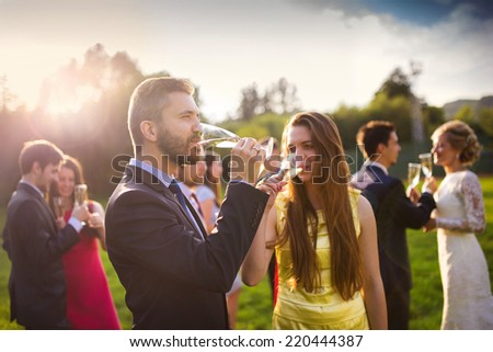 Wedding guests drinking champagne while the newlyweds clinking glasses in the background - stock photo