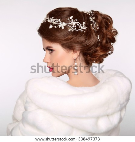 Wedding Hairstyle. Attractive girl in white fur coat. Jewelry Earring. Expressive eyes stare. Elegant lady isolated on studio white background. Luxury style. - stock photo